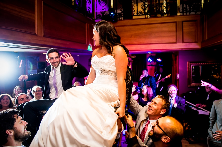 Bride and groom raised high up on their chairs during the Hora dance at their Jewish wedding at the Van Dusen Mansion