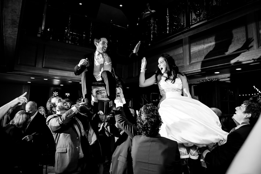 Bride and groom high five while lifted up on their chairs during their Hora dance at their Jewish wedding at the Van Dusen Mansion