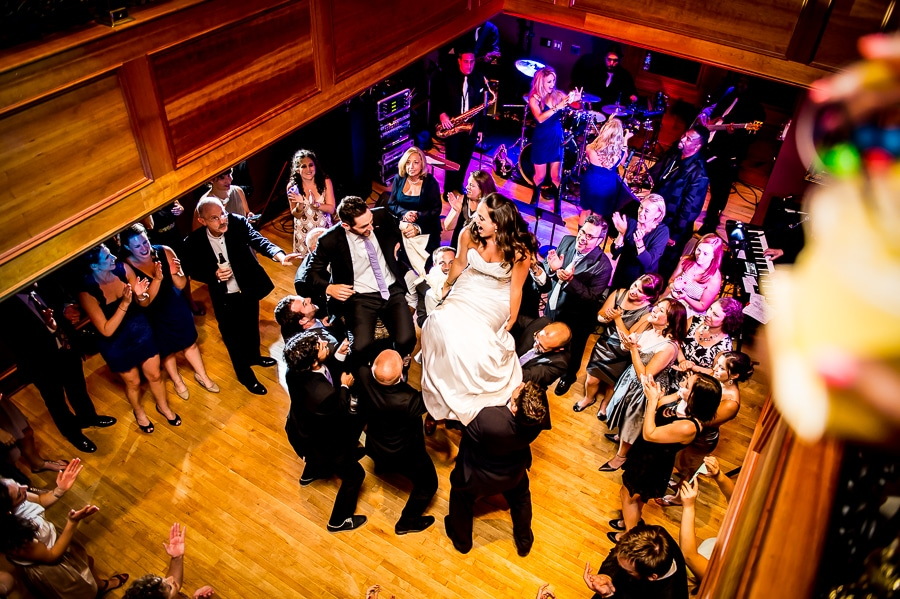 Bride & groom are raised in their chairs during the Hora dance, a Jewish wedding tradition, during their Van Dusen Mansion wedding reception