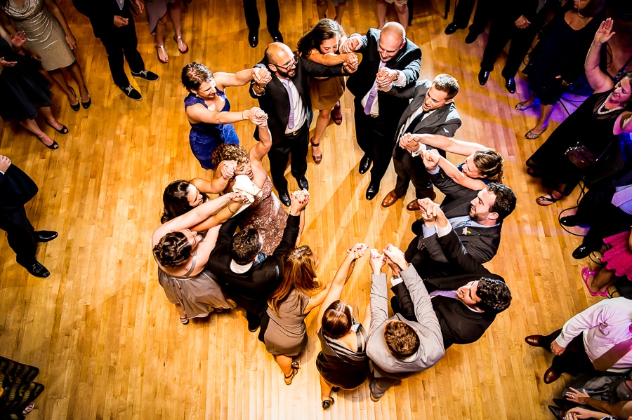 Wedding guest circled up on the dance floor with arms raised high