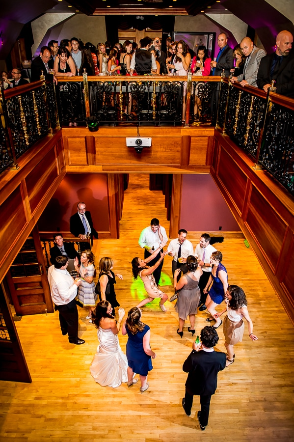 Wide angle overview shot of the dance floor and upper balcony as wedding guest enjoy the reception space at the Van Dusen Mansion