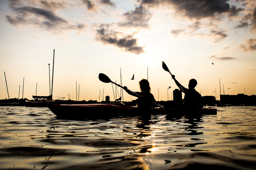 Lake Calhoun Engagement Session photo of a couple kayaking in silhouette with the sun setting in the background
