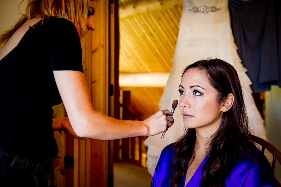 Bride getting her makeup done with her wedding dress hanging behind her in a beautiful lakeside log cabin before her Wallowa Lake destination wedding