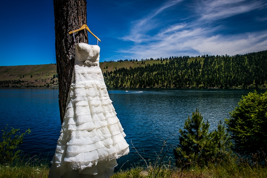 Wedding dress hangs in a tree with Wallowa Lake in the background