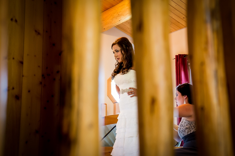 View thru a unique hand-carved wooden railing as the bride puts on her wedding dress during her Oregon destination wedding on Wallowa Lake