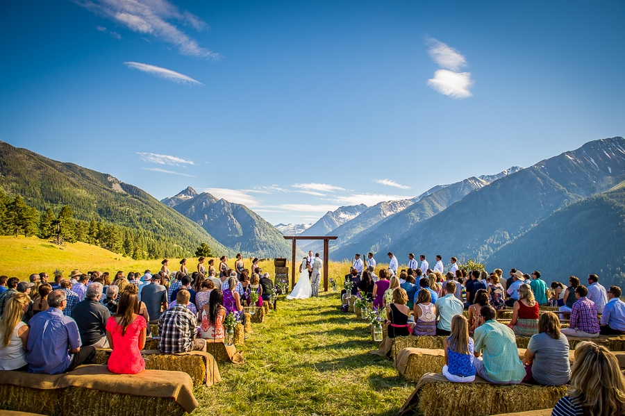 One-of-a-kind wedding ceremony location in Joseph, Oregon that overlooks Wallowa Lake and shows the bride and groom standing up at the altar, with the stunning views of the Wallowa Mountains behind them.