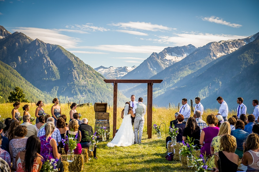 Telephoto image of the stunning wedding ceremony location in Joseph, OR that shows the grandness of the Wallowa mountain range behind them and is reminiscent of the mountains scenes (and hilariously famous memes) from the classic movie, The Sound of Music.