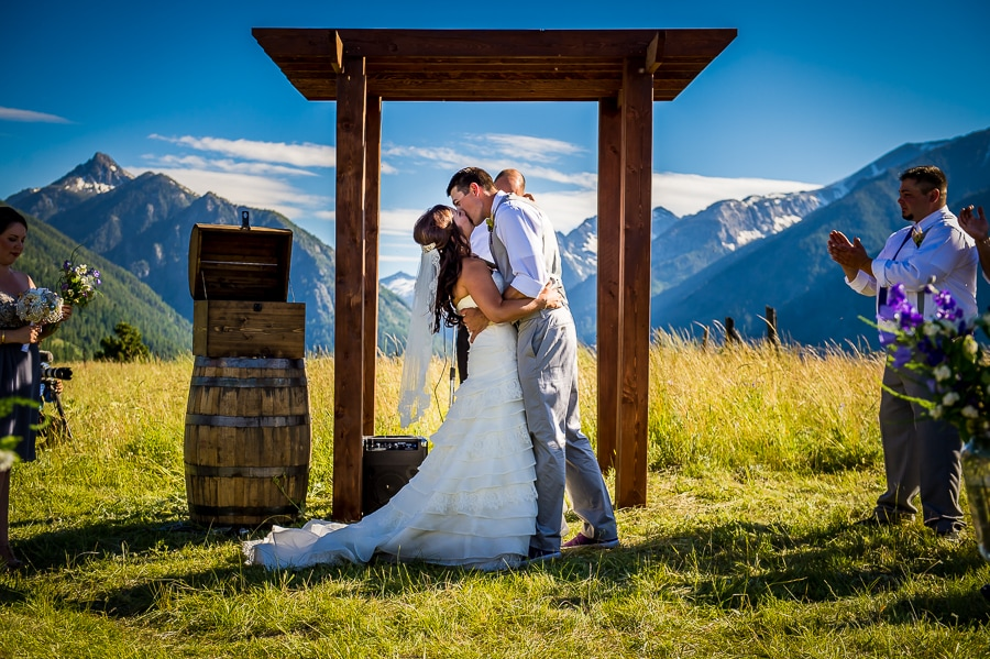 Bride & Groom share their first kiss up at the altar with a stunning mountainous background behind them during their Wallowa Lake wedding in Joseph, OR