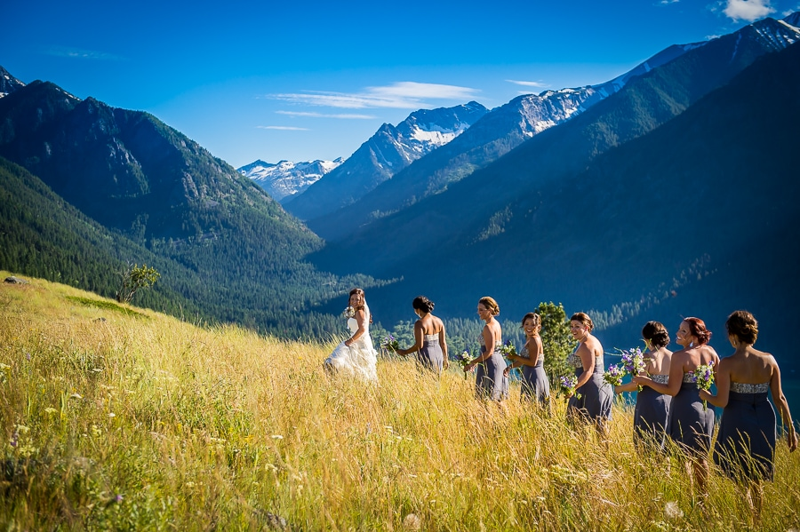 The bride and her bridesmaids walking through the grassy fields with the massive Wallowa Mountains behind them during a super fun Oregon destination wedding