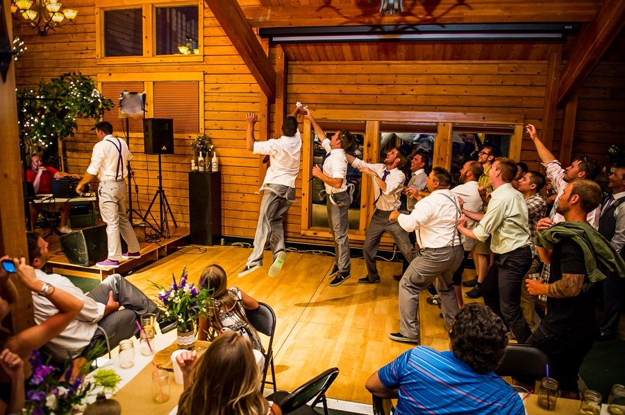 The brides brother makes and epic leap to grab the garter during the garter toss section of the wedding reception at the Josephy Center for Arts and Culture