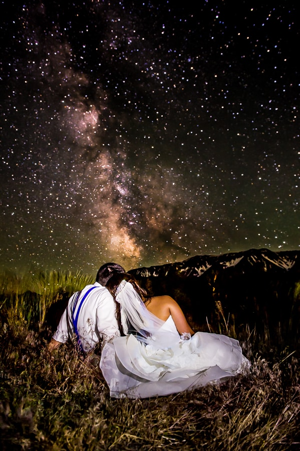 Bride and groom sit under an absolutely brilliantly lit starry night sky, facing the Wallowa Mountains, on their wedding day
