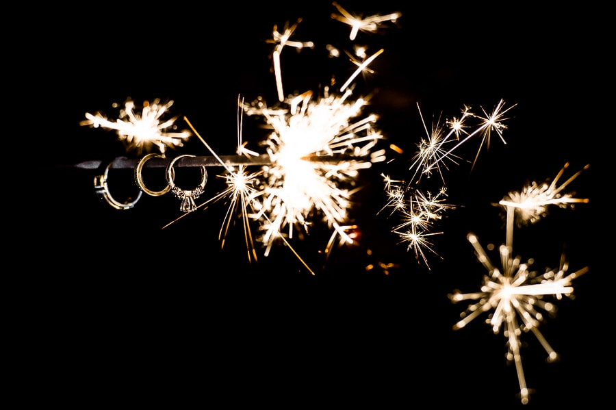 Close up of wedding rings hanging from a lit sparkler during a Wallowa Lake Wedding in Joseph, Oregon