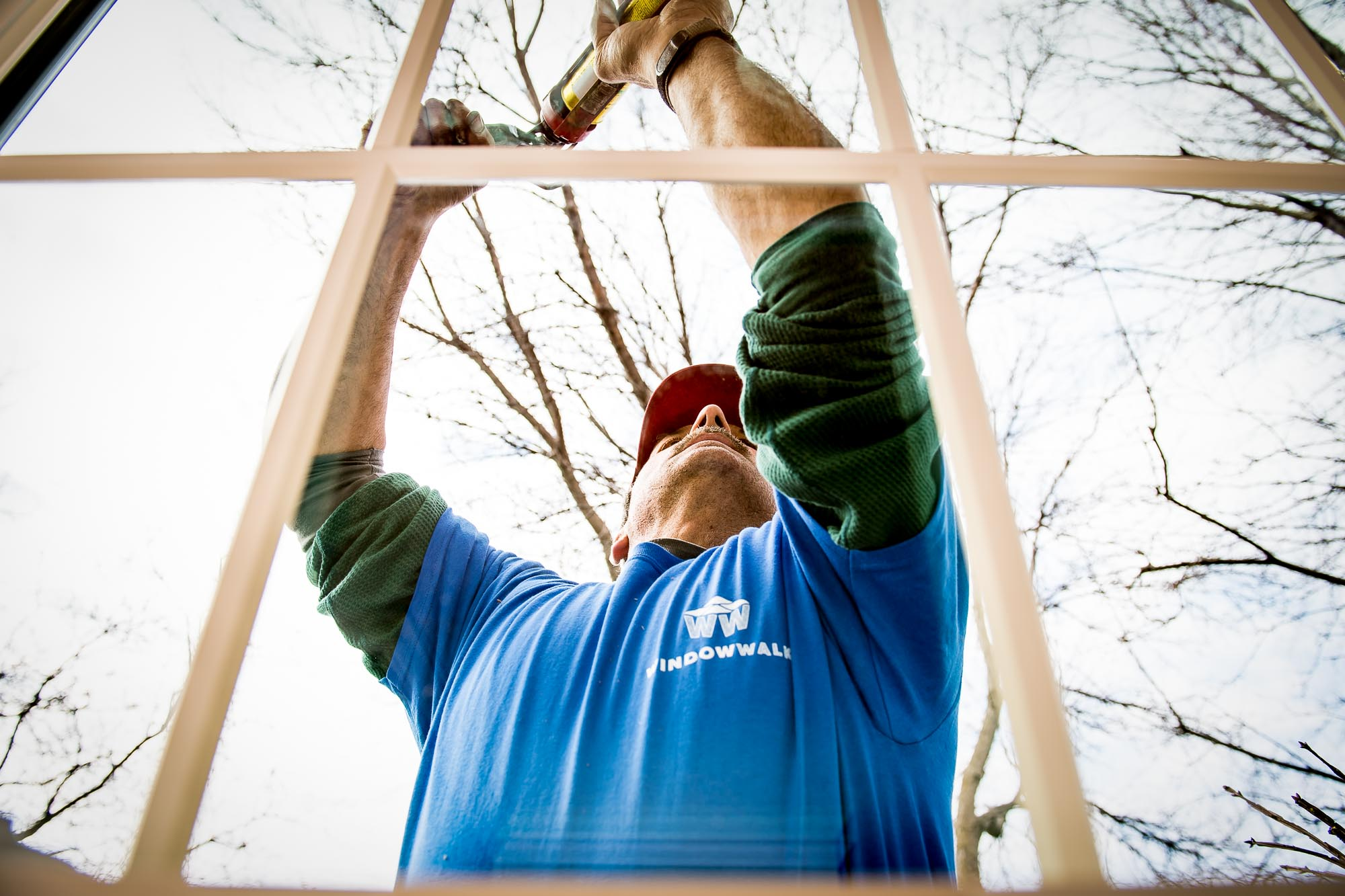 Commercial photograph of a professional window installer from a creative angle