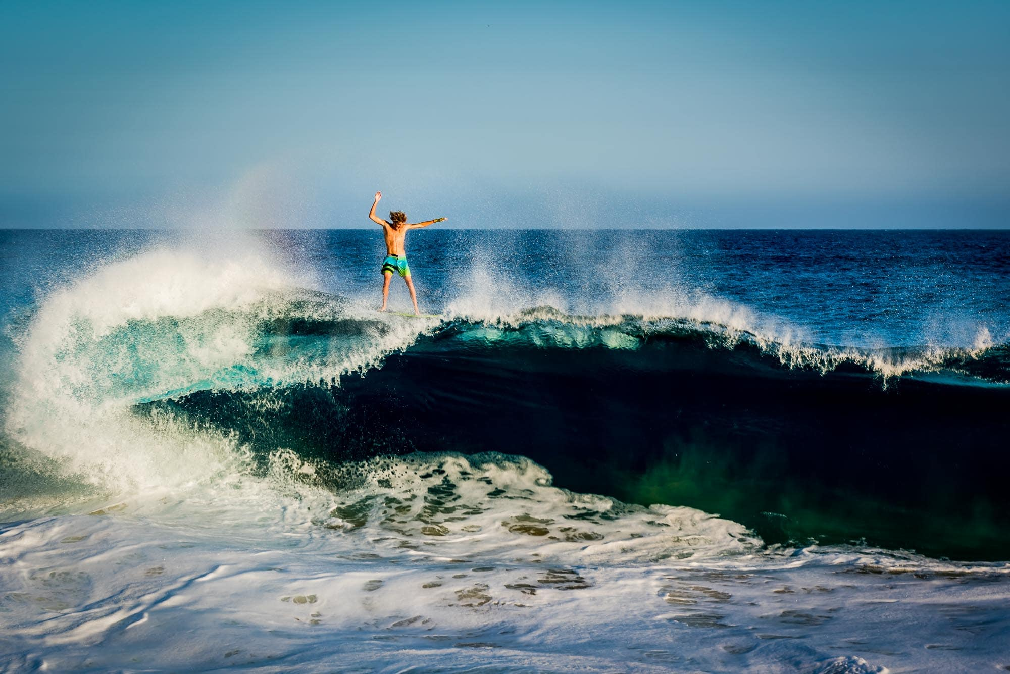 Savage of JoogSquad riding the top of an huge wave on his skimboard at Land's End in Cabo San Lucas