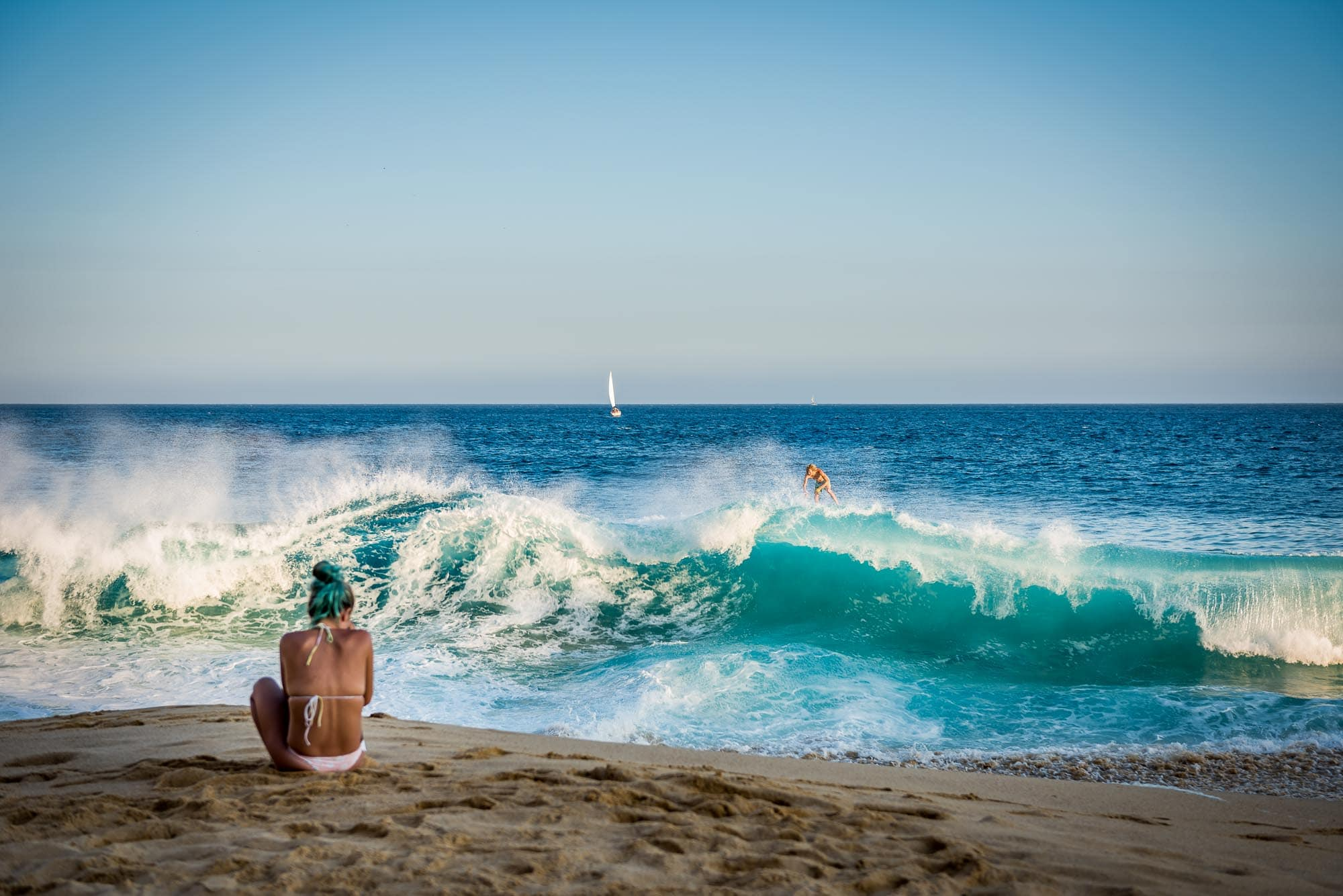 Savage of JoogSquad getting his picture taken by a girl with blue hair while he rides a wave on his skimboard at Land's End in Cabo San Lucas
