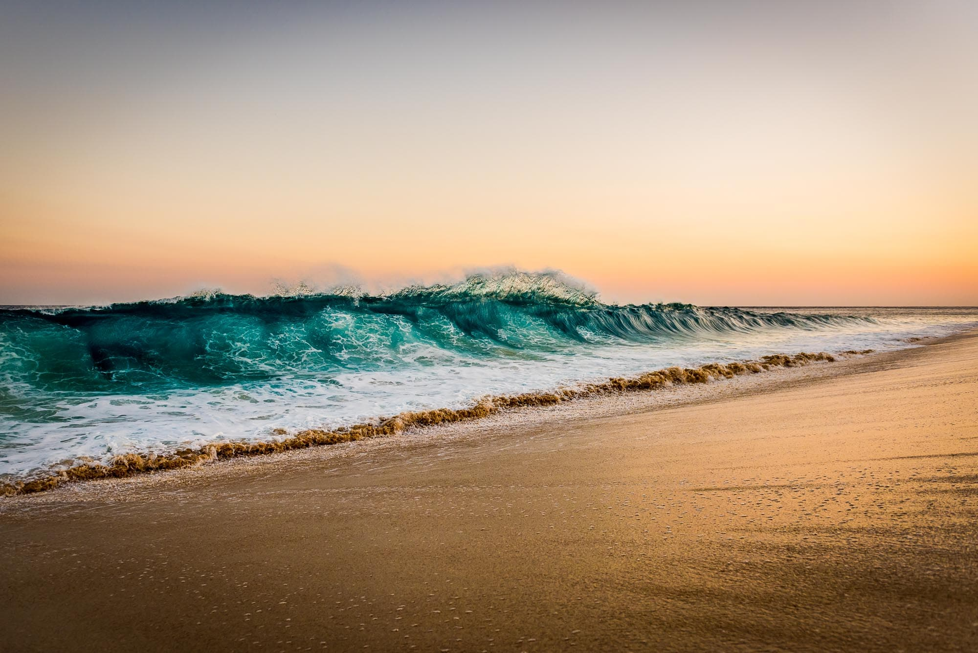 Wave crashing at sunset with the sky's color reflecting off the sand at Land's End in Cabo San Lucas