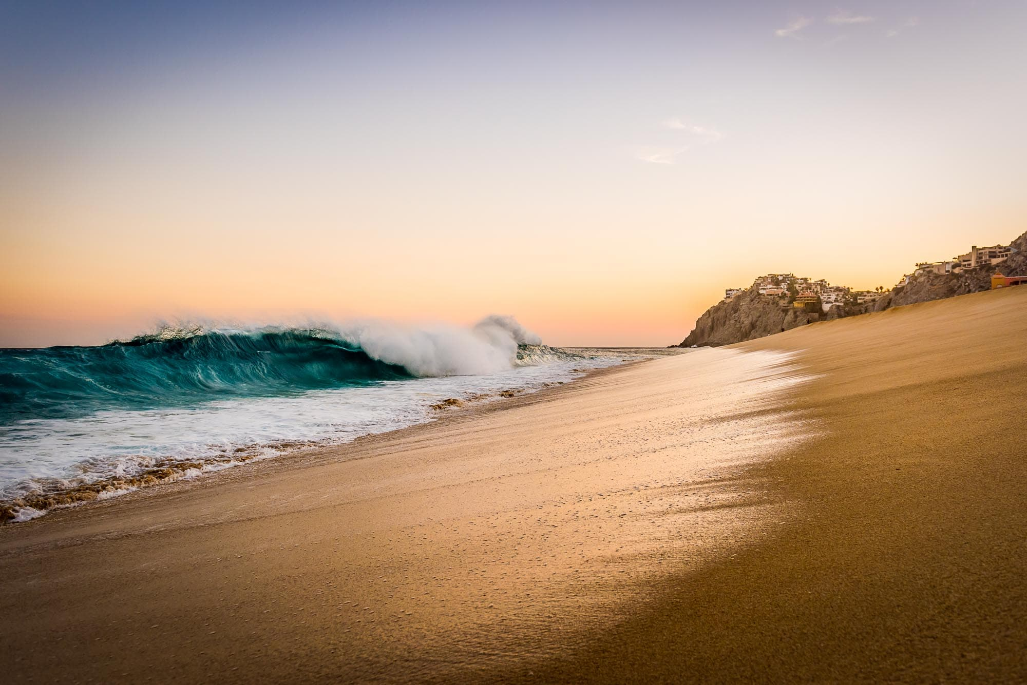 Colorful blue wave crashing during a painted sky sunset, looking the opposite way from Land's End in Cabo San Lucas