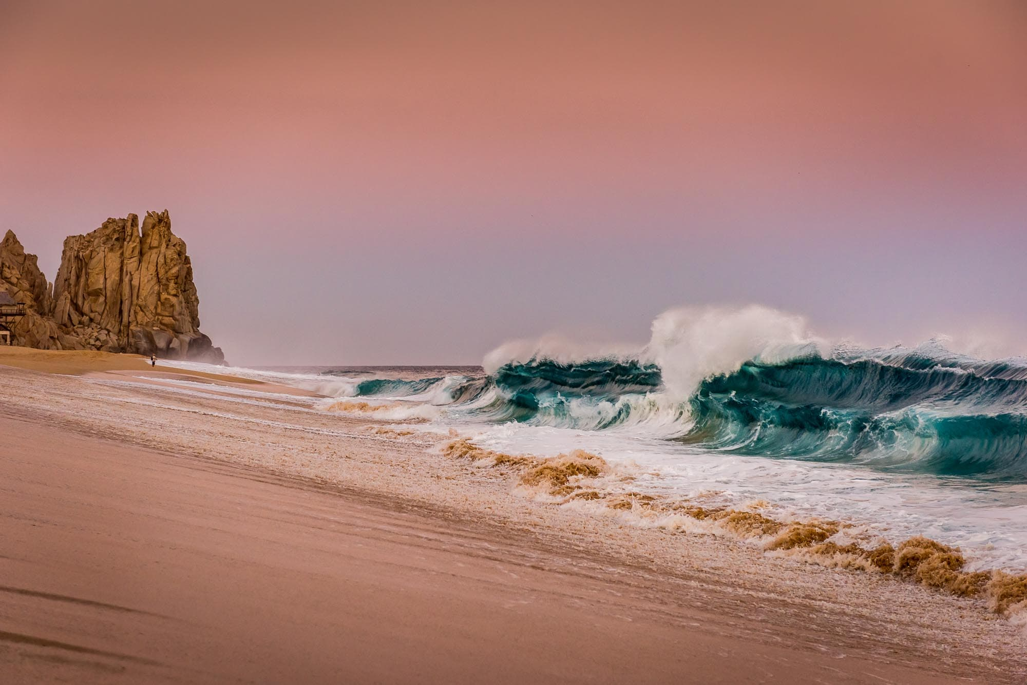 Giant doubled up wave crashing during a gorgeous sunset at Land's End in Cabo San Lucas