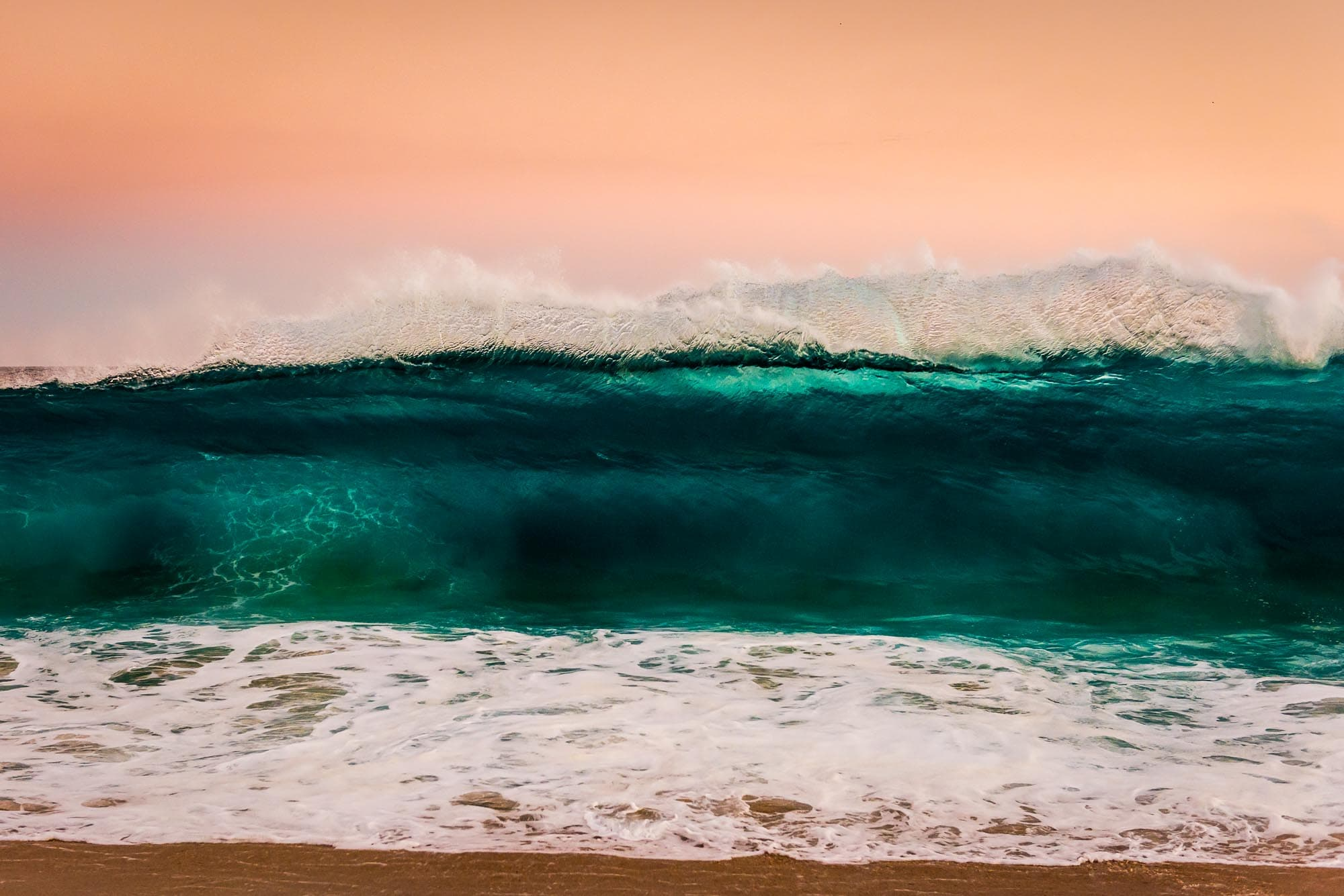 Close up of wave crashing during sunset at Land's End in Cabo San Lucas