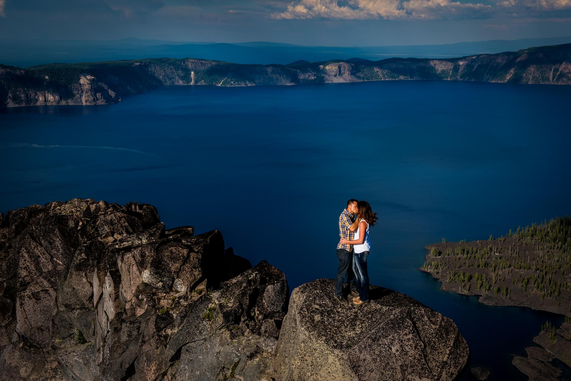Newly engaged couple sharing a kiss above Crater Lake at Watchman Lookout