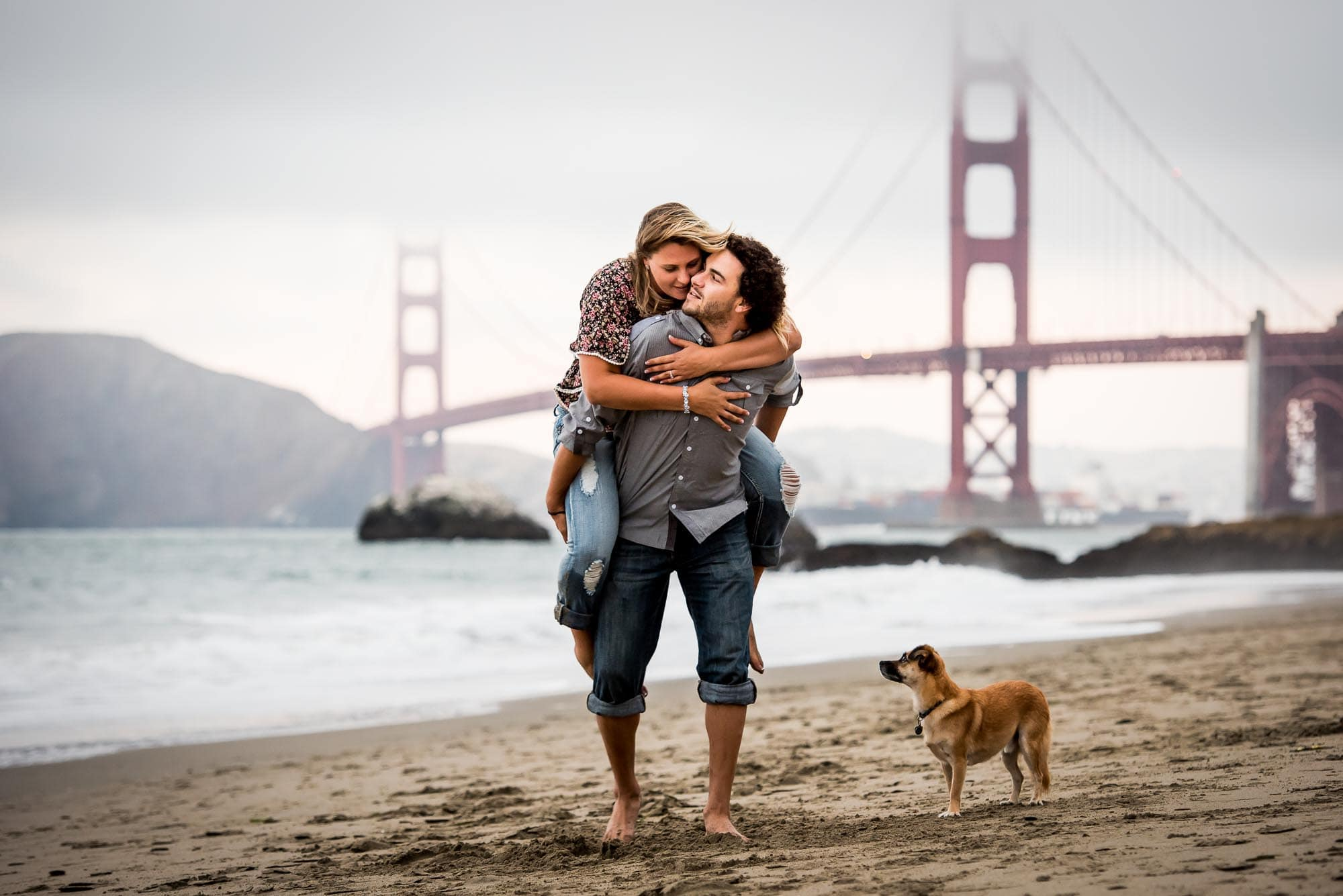 Engagement photo at Baker Beach with the Golden Gate Bridge in the background