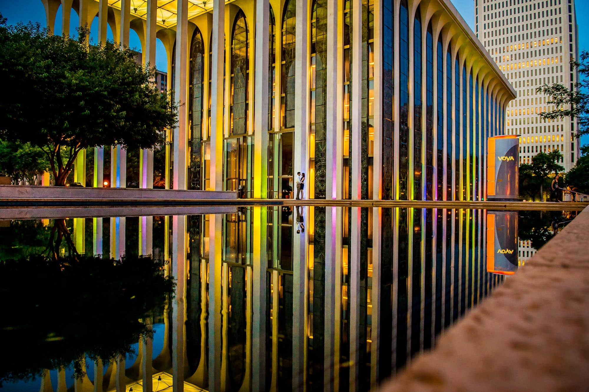Engagement photo of couple cuddling with their reflection over the water at the Voya Building in Minneapolis