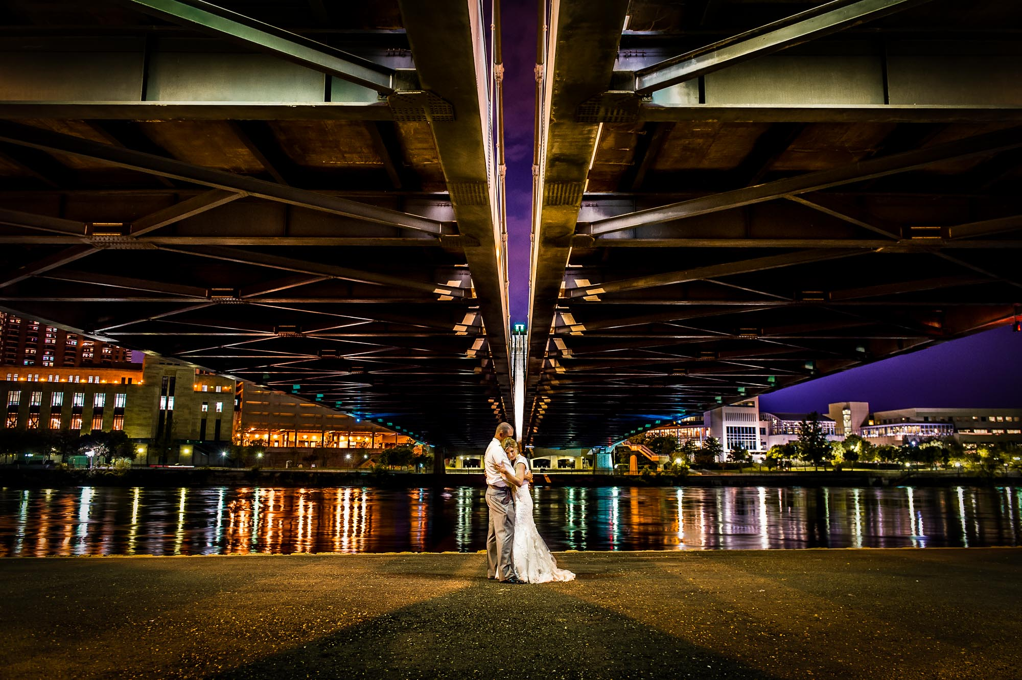 Newly married couple embracing underneath the Hennepin Avenue Bridge in Minneapolis