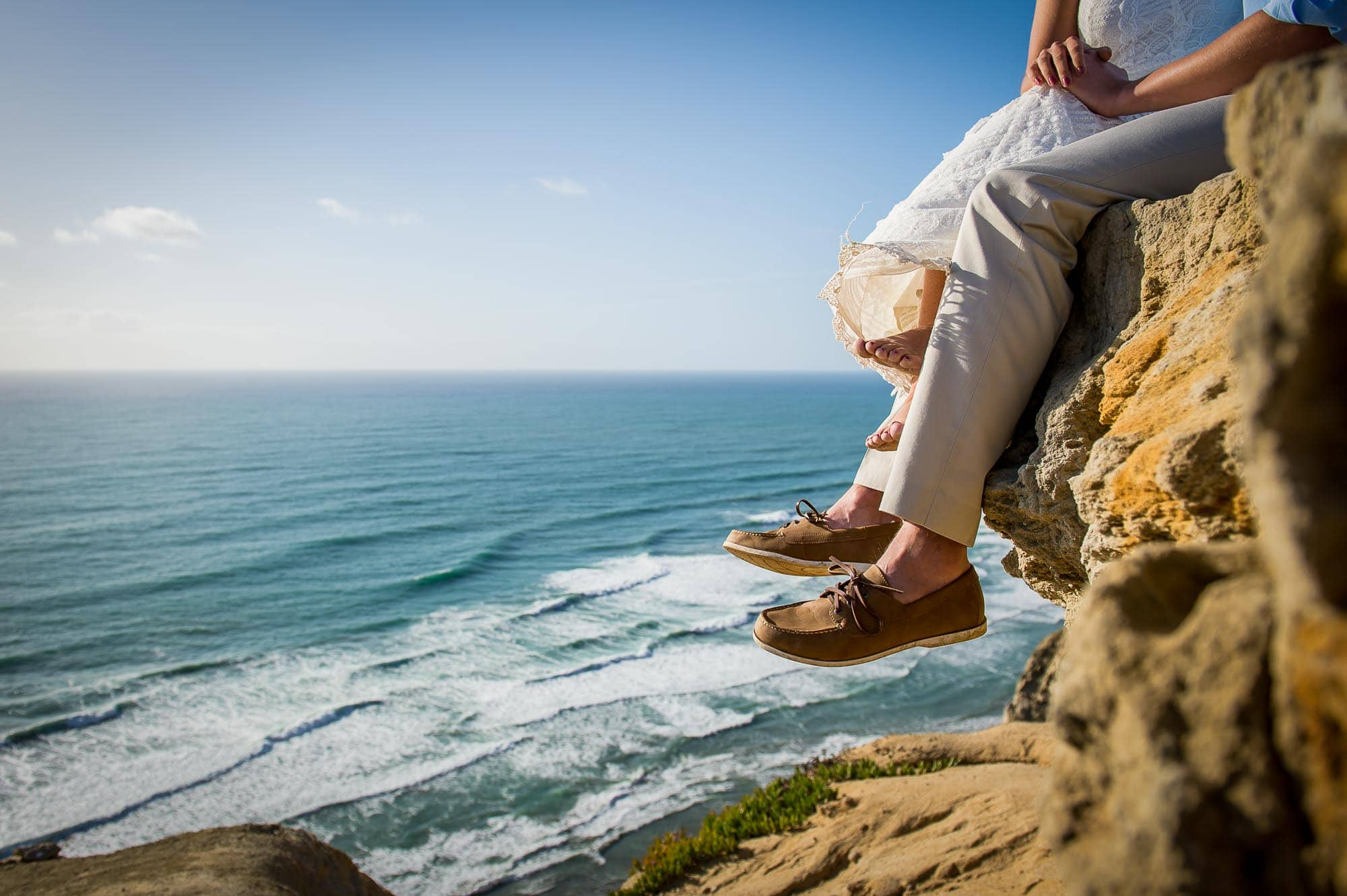 Couple sitting on a La Jolla cliff looking over the Pacific Ocean