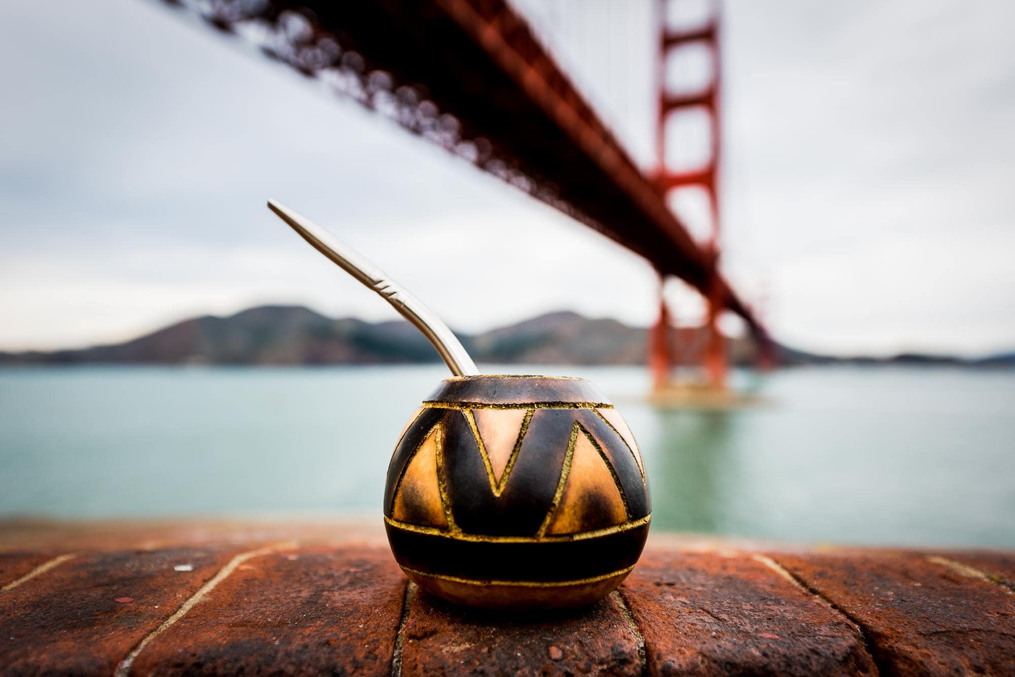 Guayaki Yerba mate gourd sitting on a red brick wall of Fort Point perfectly centered under the golden gate bridge