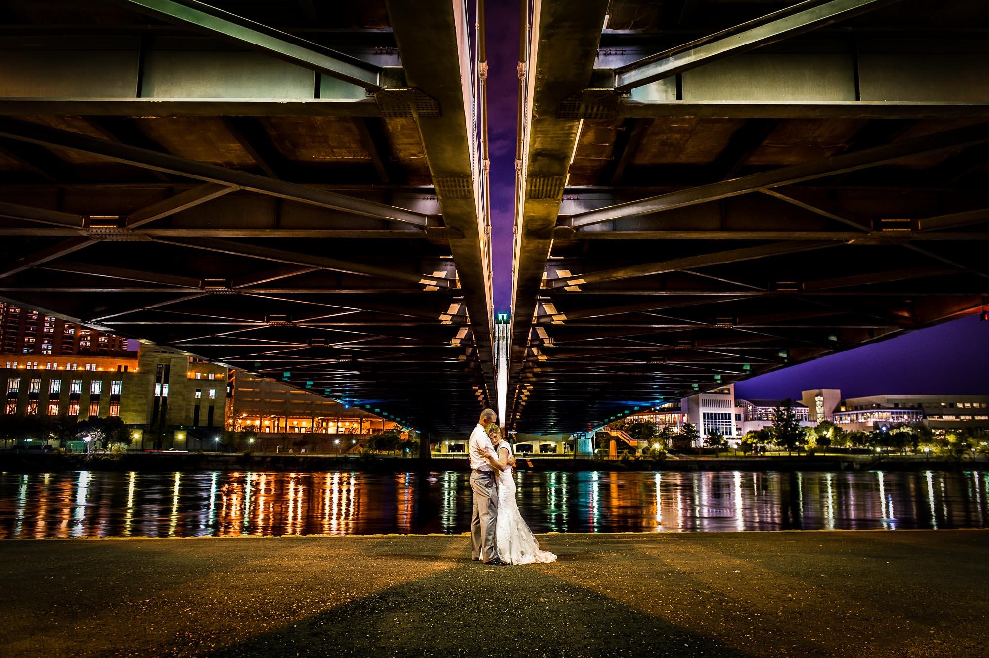 Nighttime wedding photo in Minneapolis underneath the Hennepin Bridge