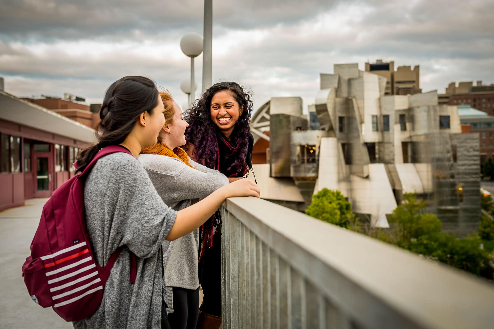 University of Minnesota students laughing with each other with the Weisman Art Museum in the background