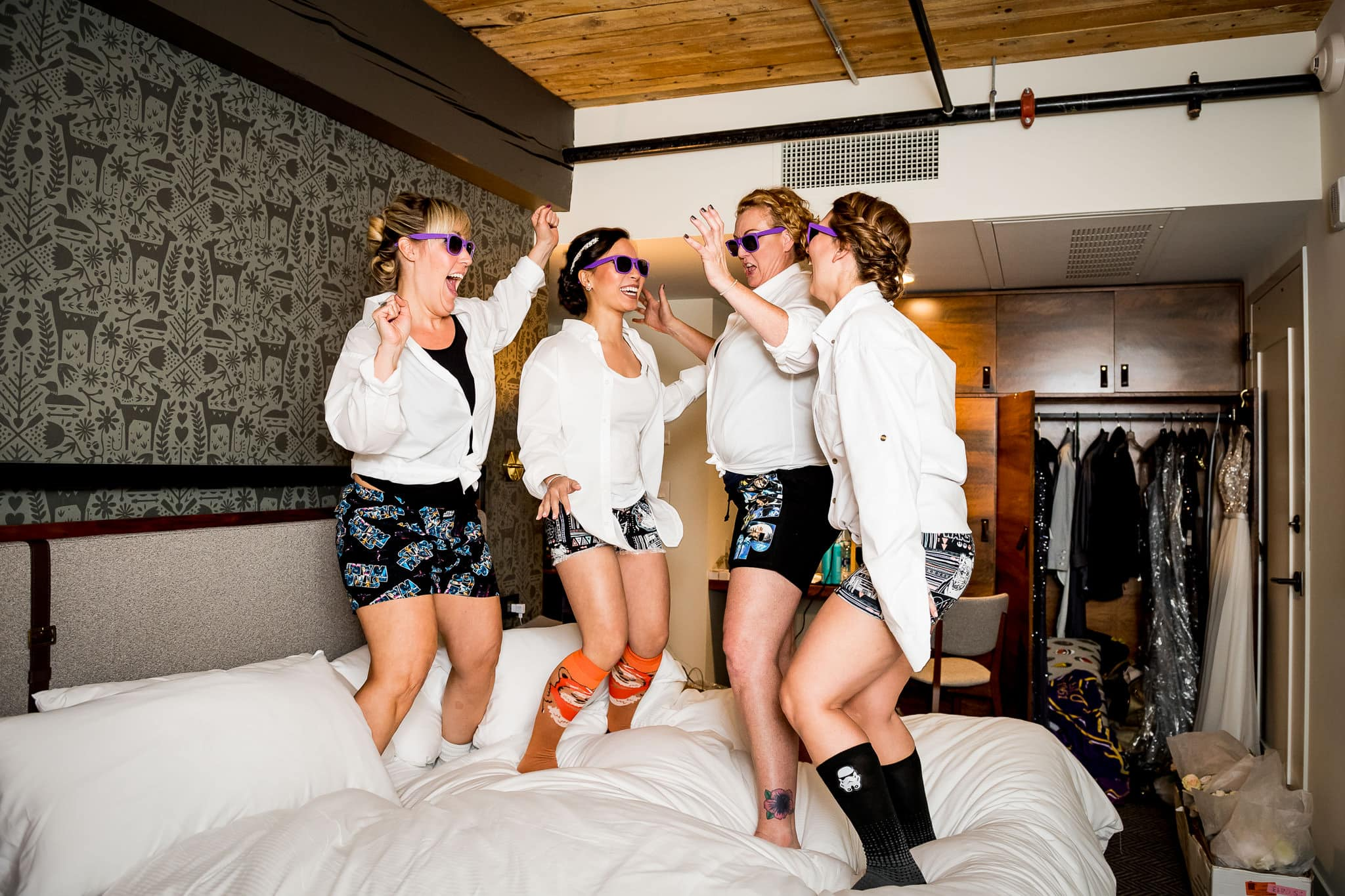 Bridesmaids jumping on the bed at the Hewing Hotel