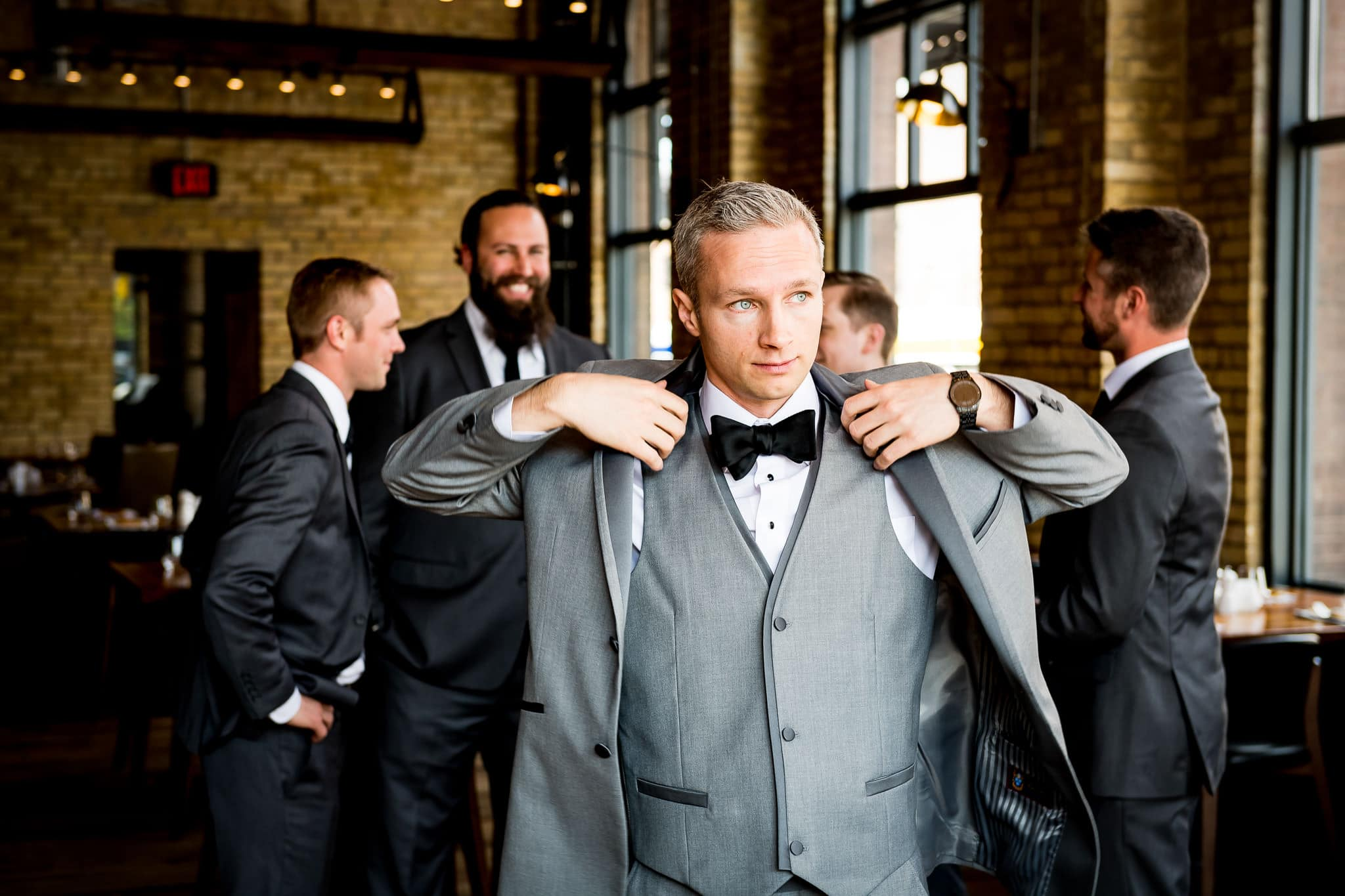Groom puts on jacket at Hewing Hotel