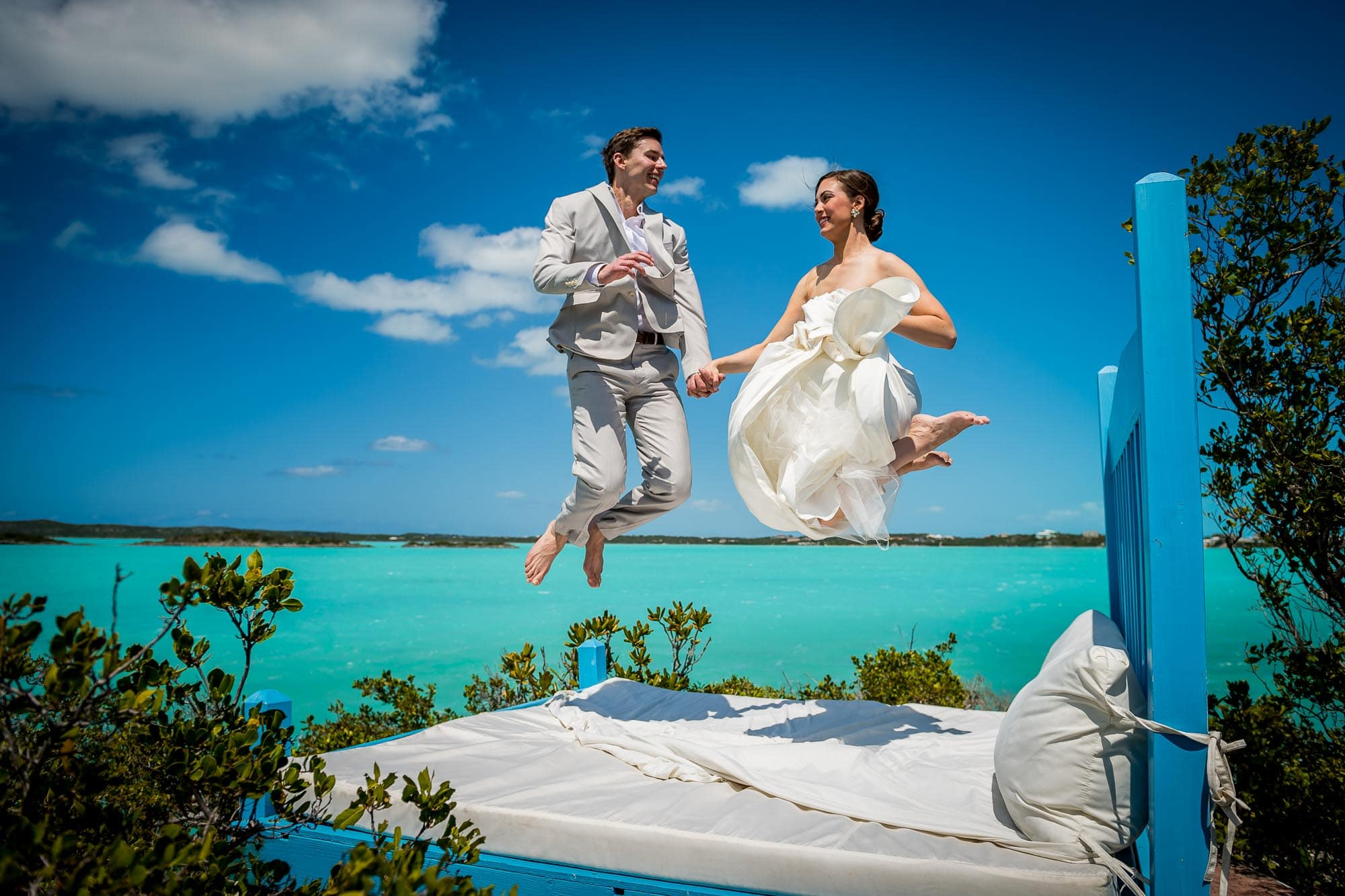 destination wedding photography of a bride and groom jumping on an outdoor bed over the brilliant blue water of Chalk Sound on the island of Turks and Caicos