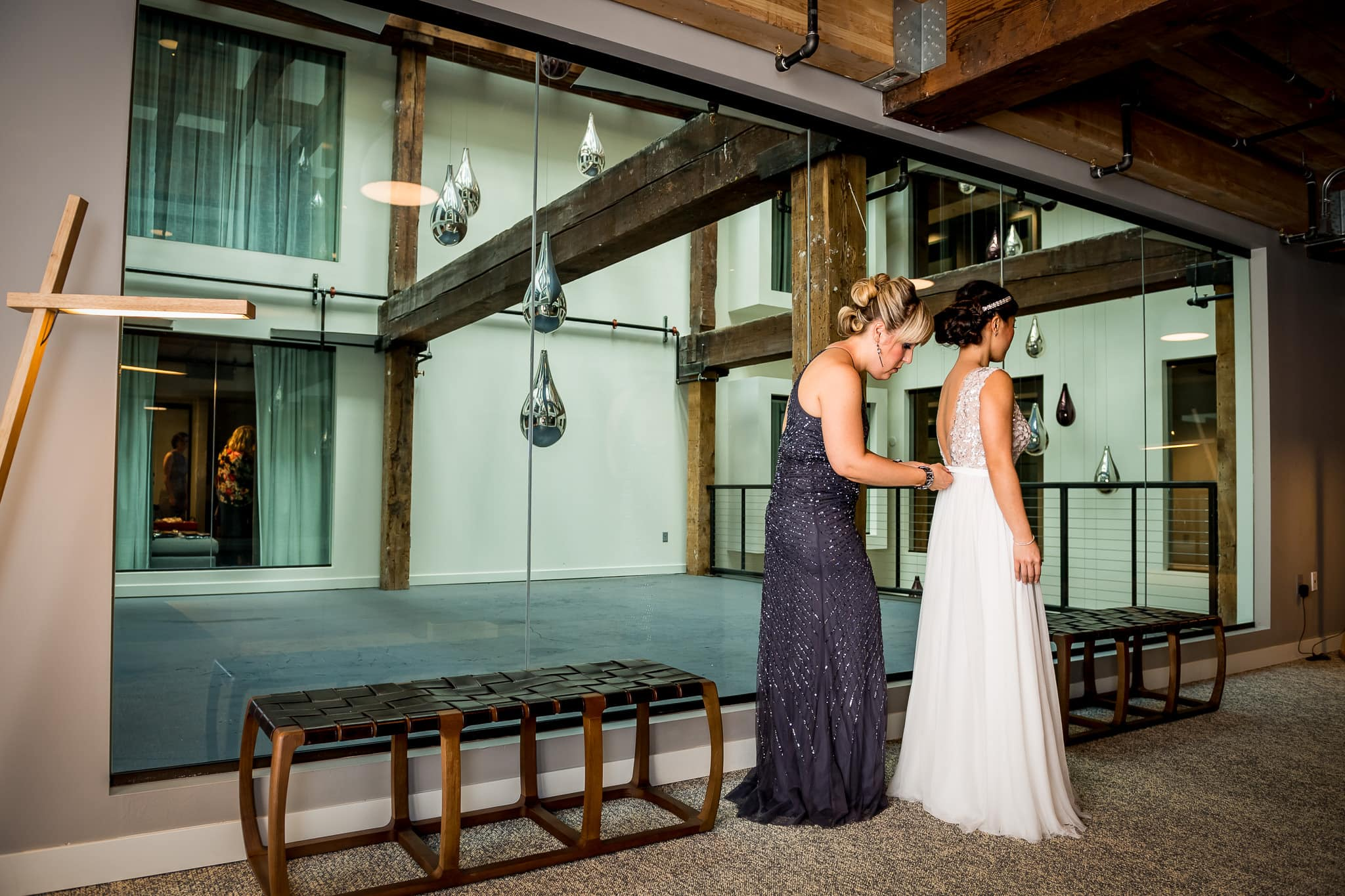 Bride getting into her dress at the Hewing Hotel