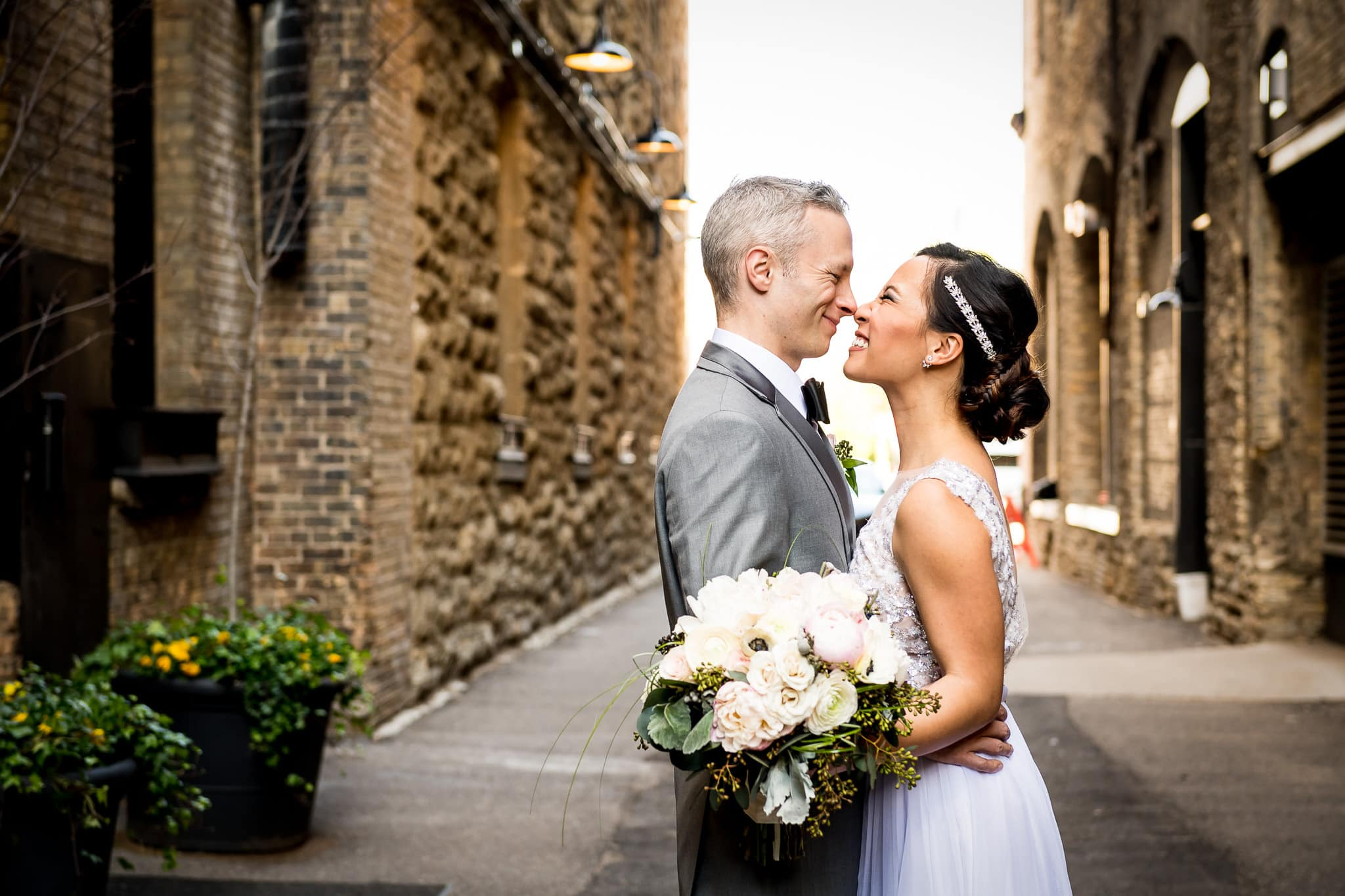Bride and Groom Eskimo kisses in the alley behind the Hewing Hotel
