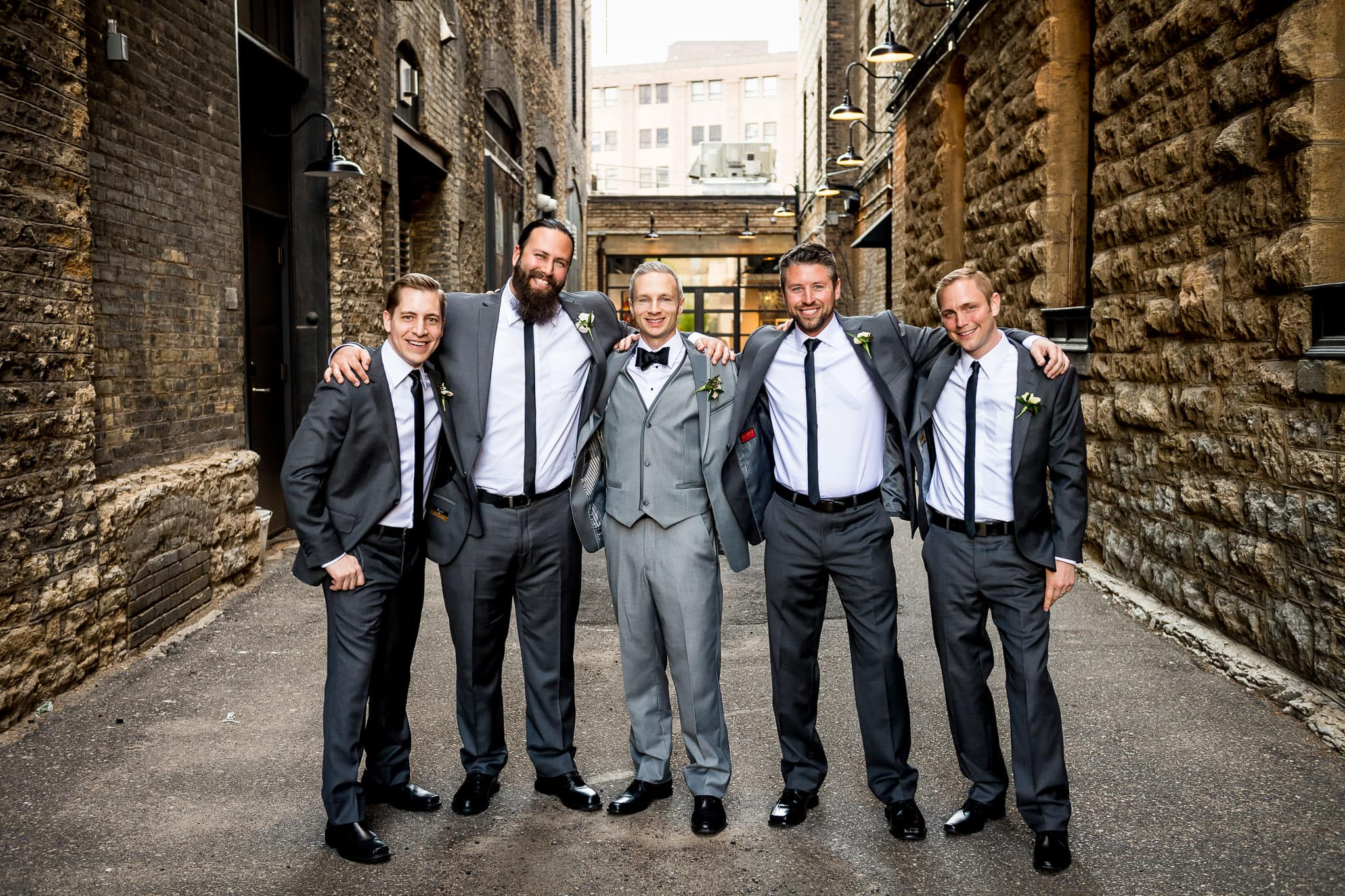 Groomsmen together in the alley behind the Hewing Hotel
