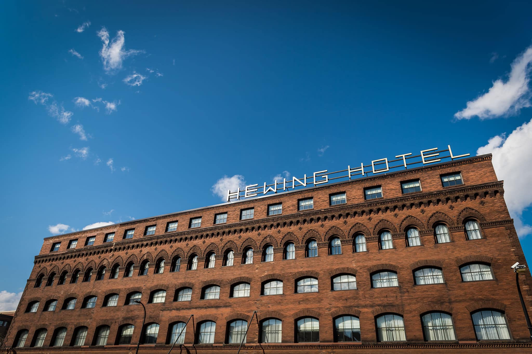 Hewing Hotel building with bright blue sky and some puffy white clouds