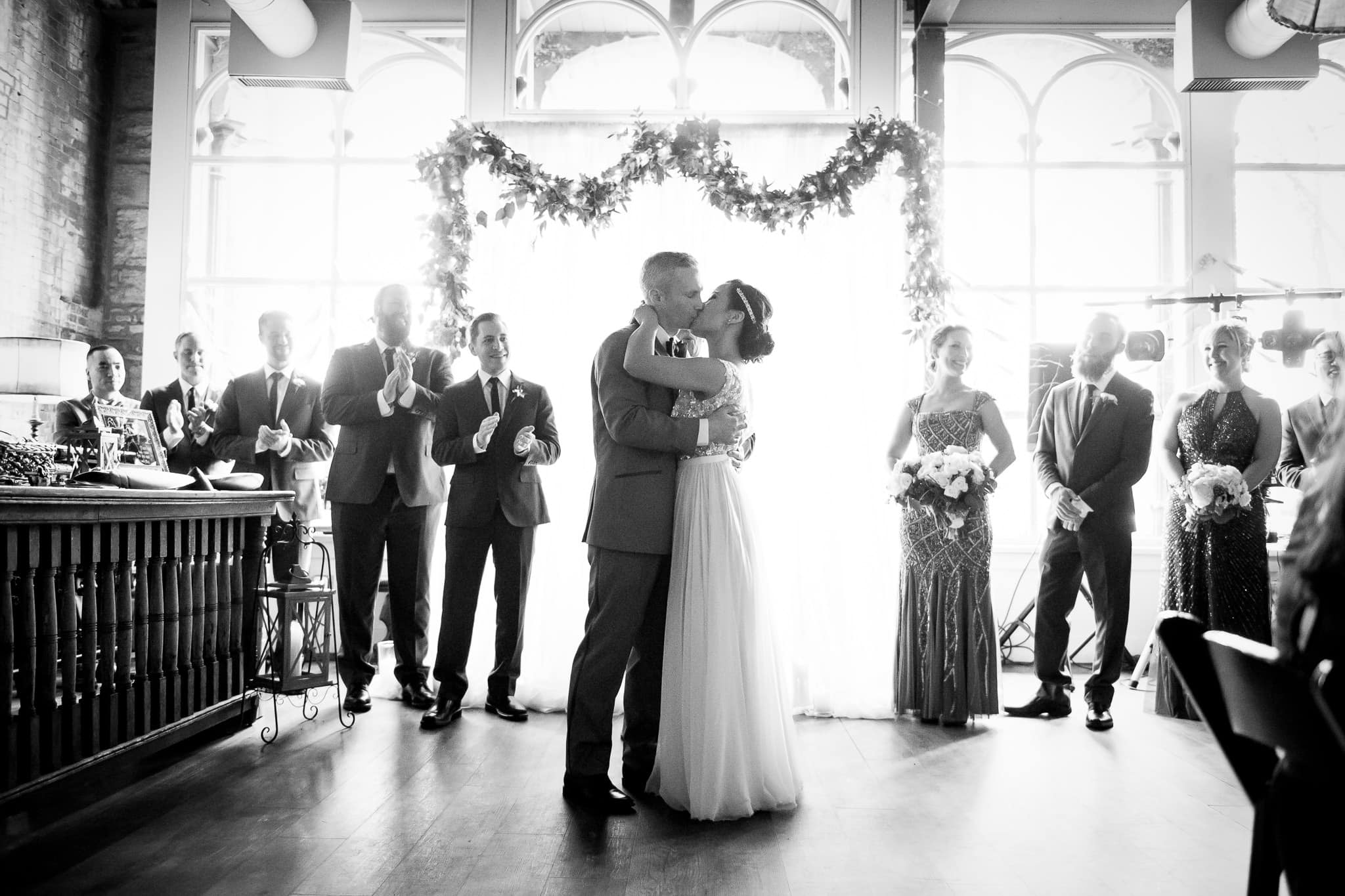 Bride and Groom first kiss in the River Room at Aster Cafe Wide Angle