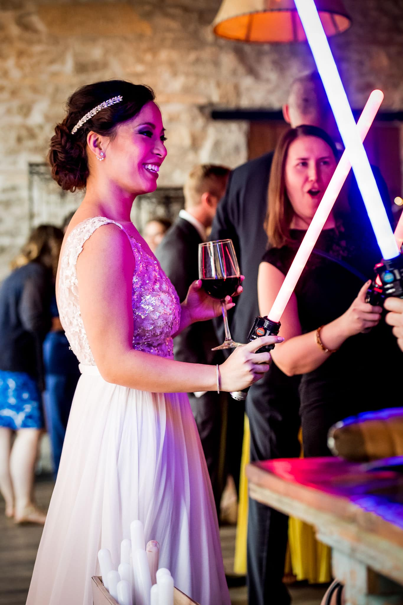 Bride with her Star Wars Light Saber during the wedding reception in the River Room at Aster Cafe 1