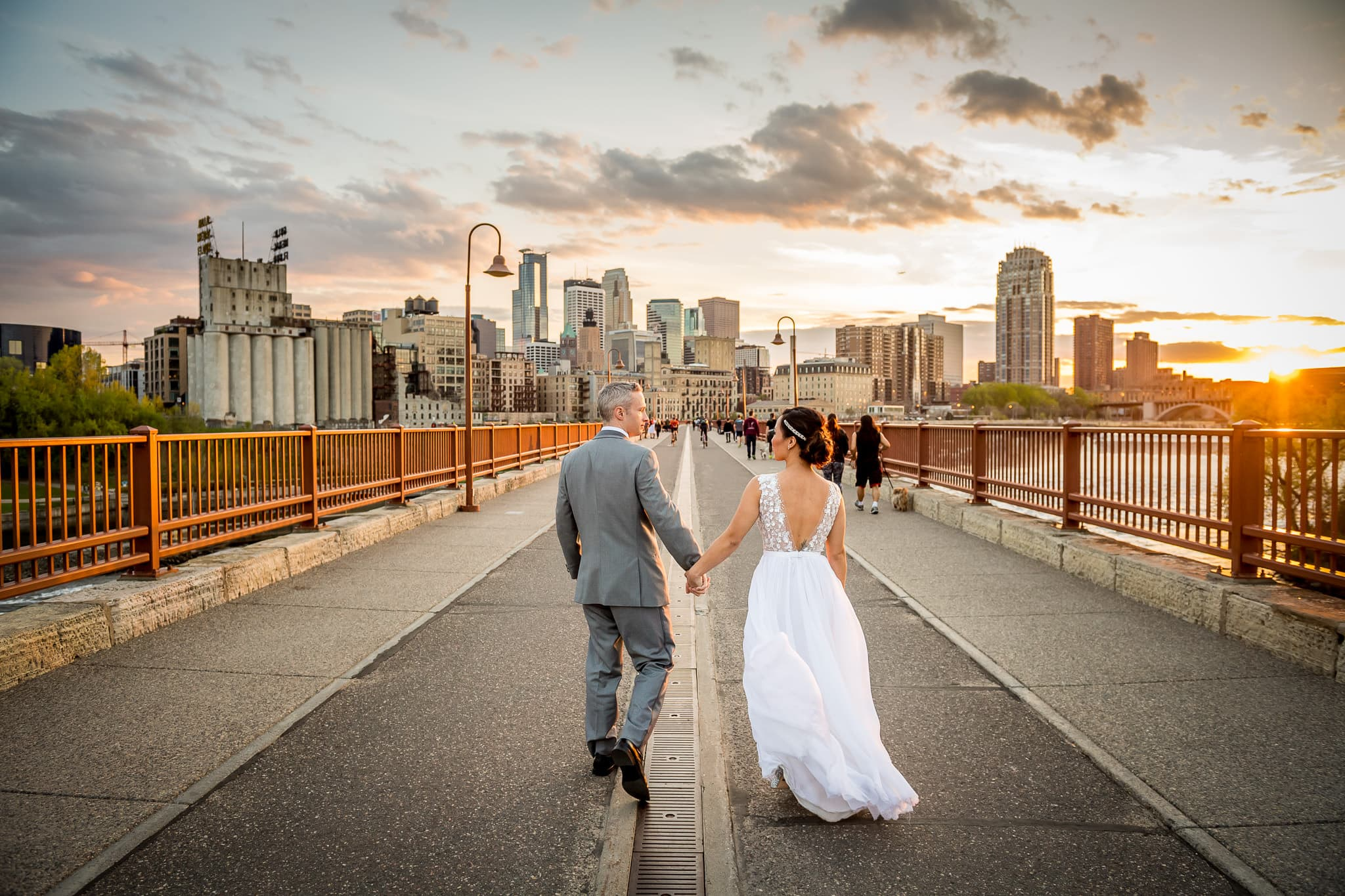 Bride and Groom walking across the Stone Arch Bridge in Saint Anthony Main at Sunset