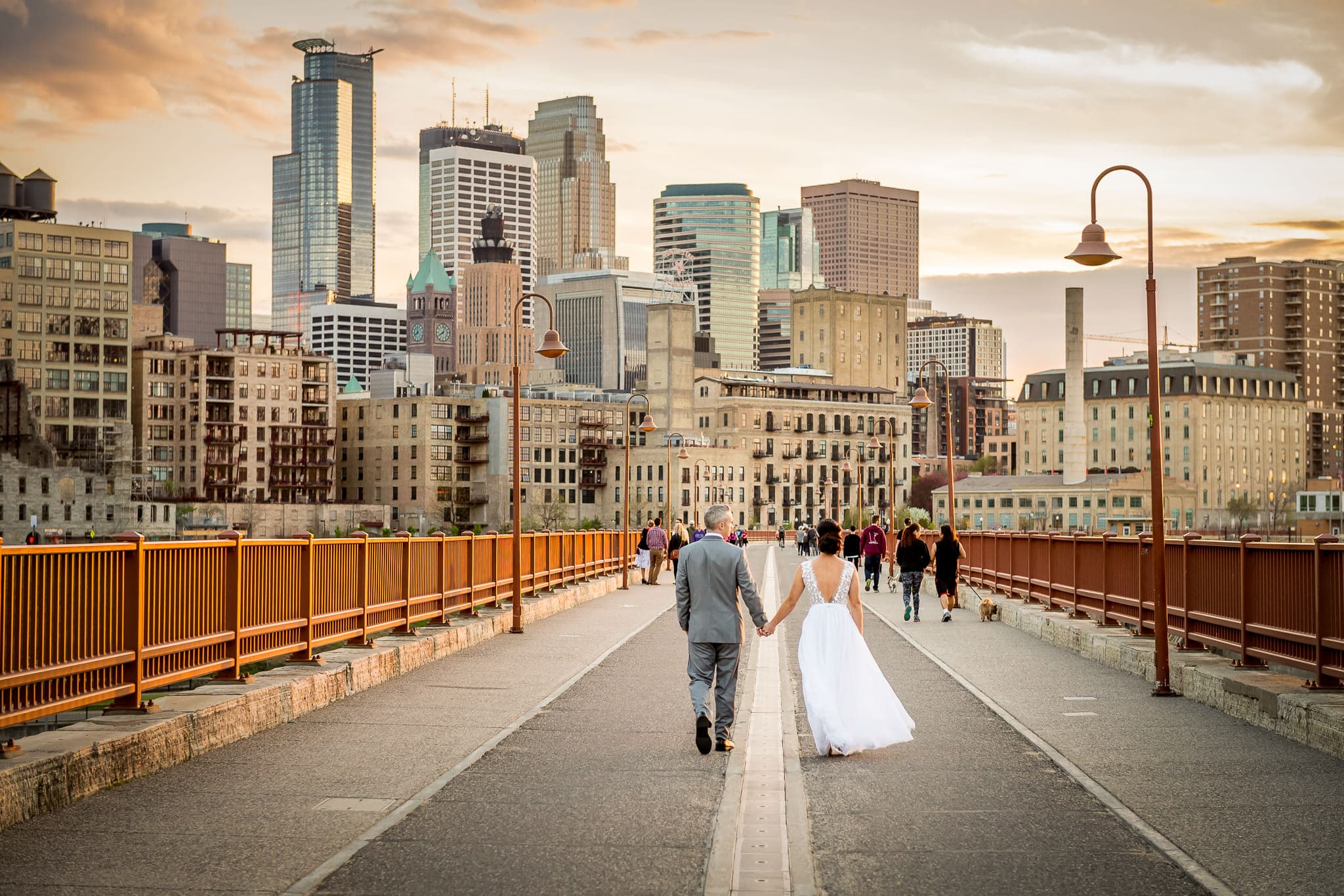 Bride and Groom walking across the Stone Arch Bridge in Saint Anthony Main with Minneapolis Skyline in the Background at Sunset