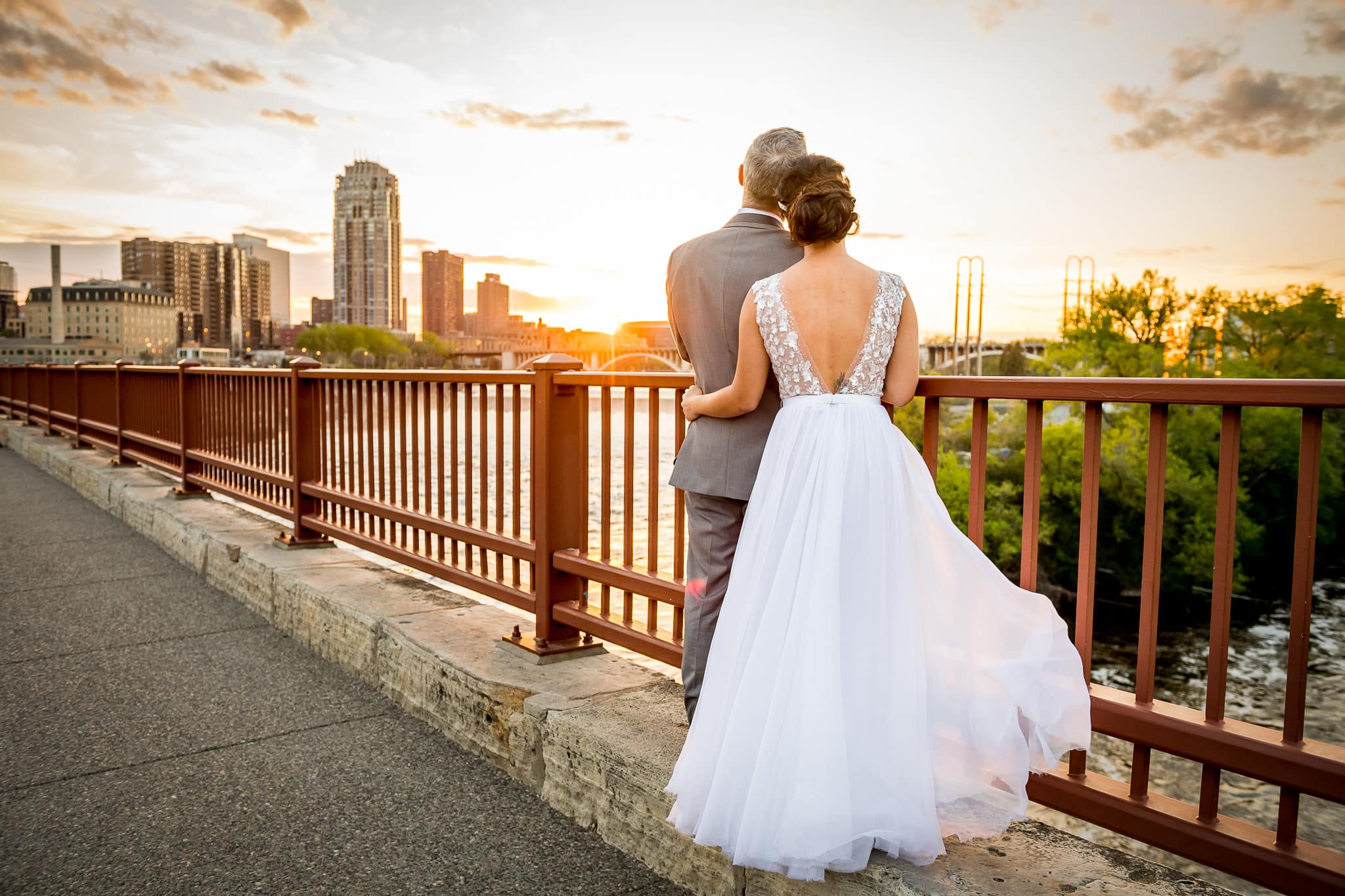 Bride and Groom embrace as the watch the sunset from the Stone Arch Bridge in Minneapolis