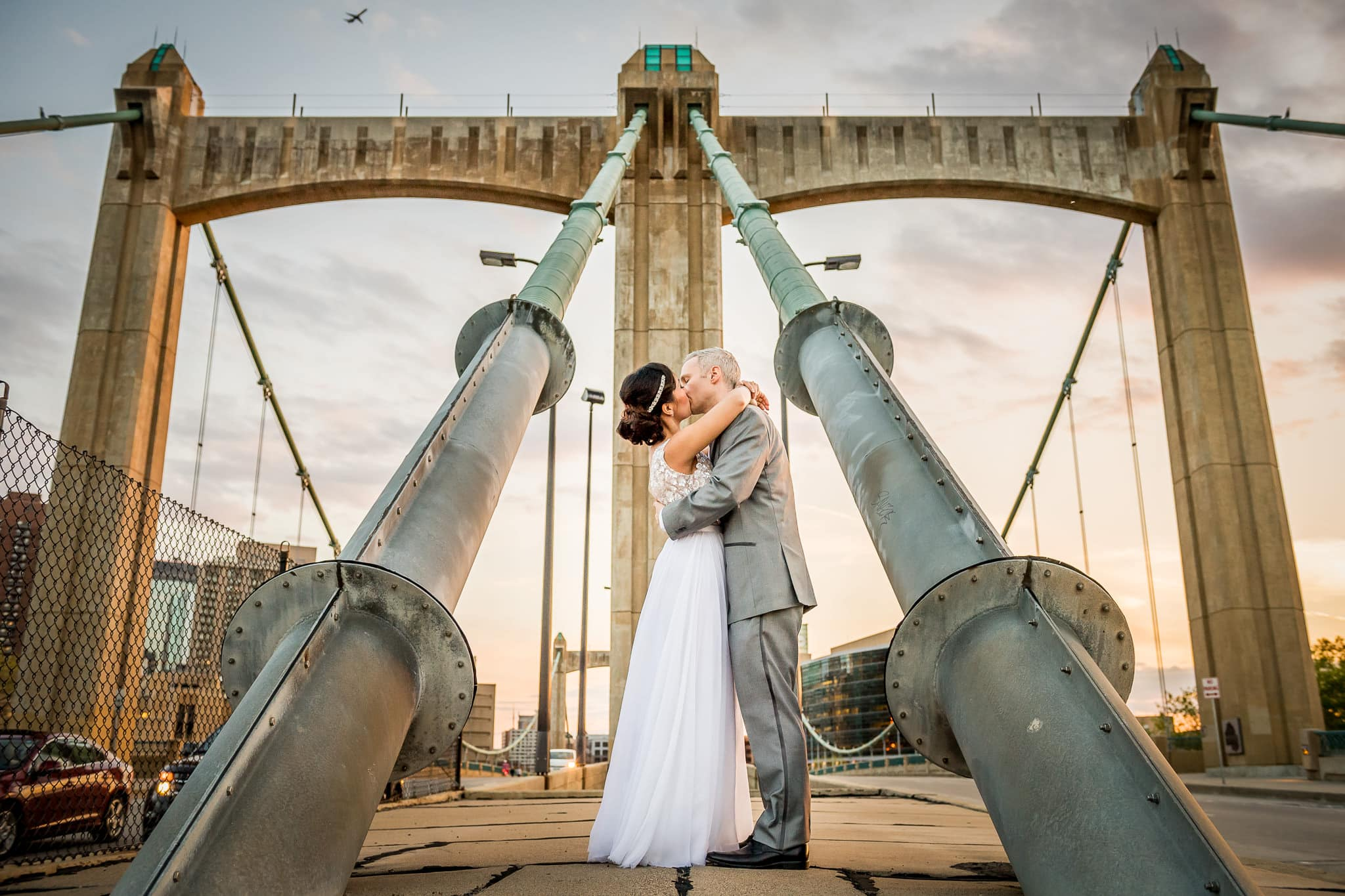 Bride and Groom kissing on the Hennepin Avenue Bridge with Airplane in Background
