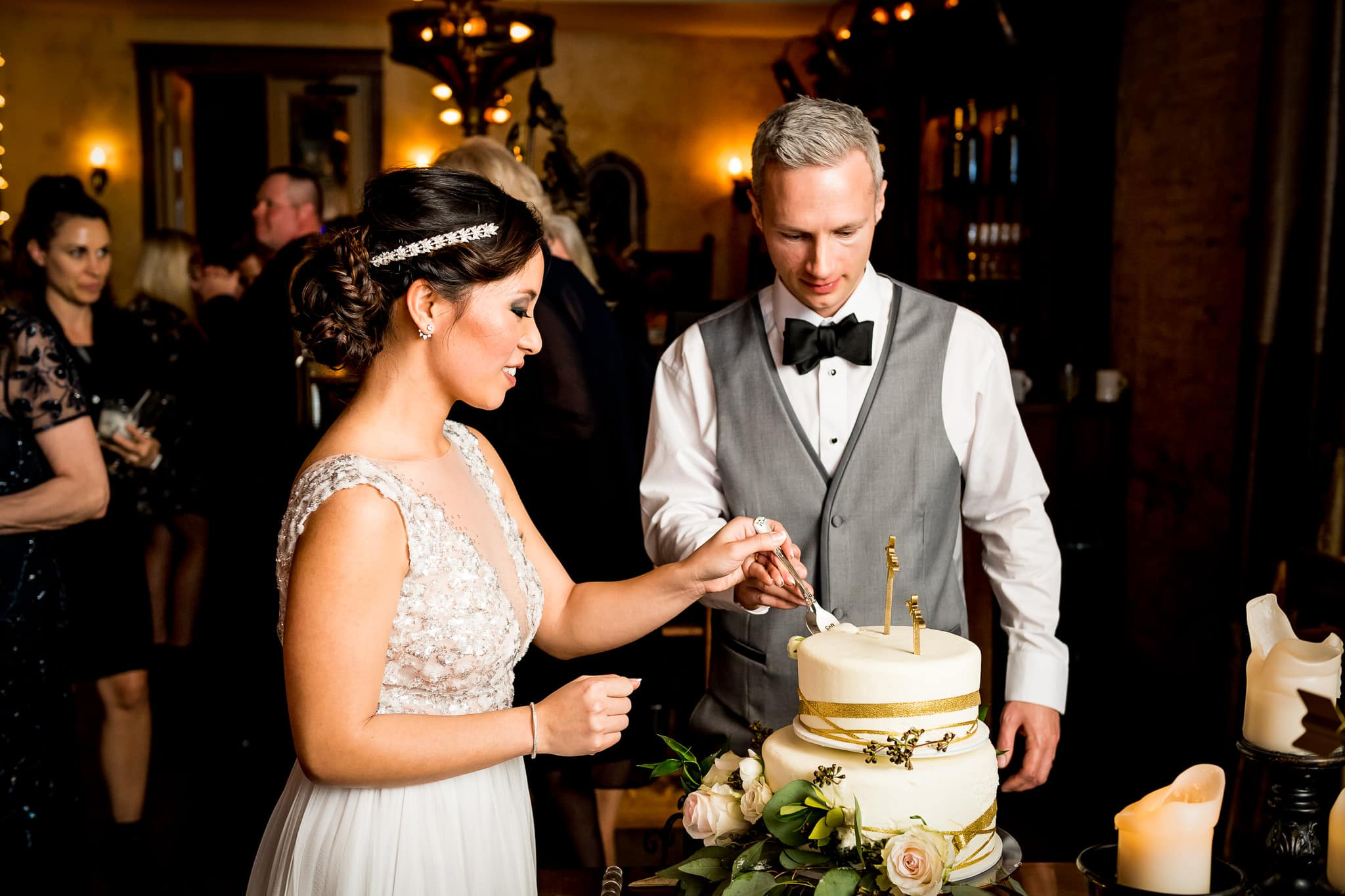Bride and Groom cutting their cake in the River Room at Aster Cafe