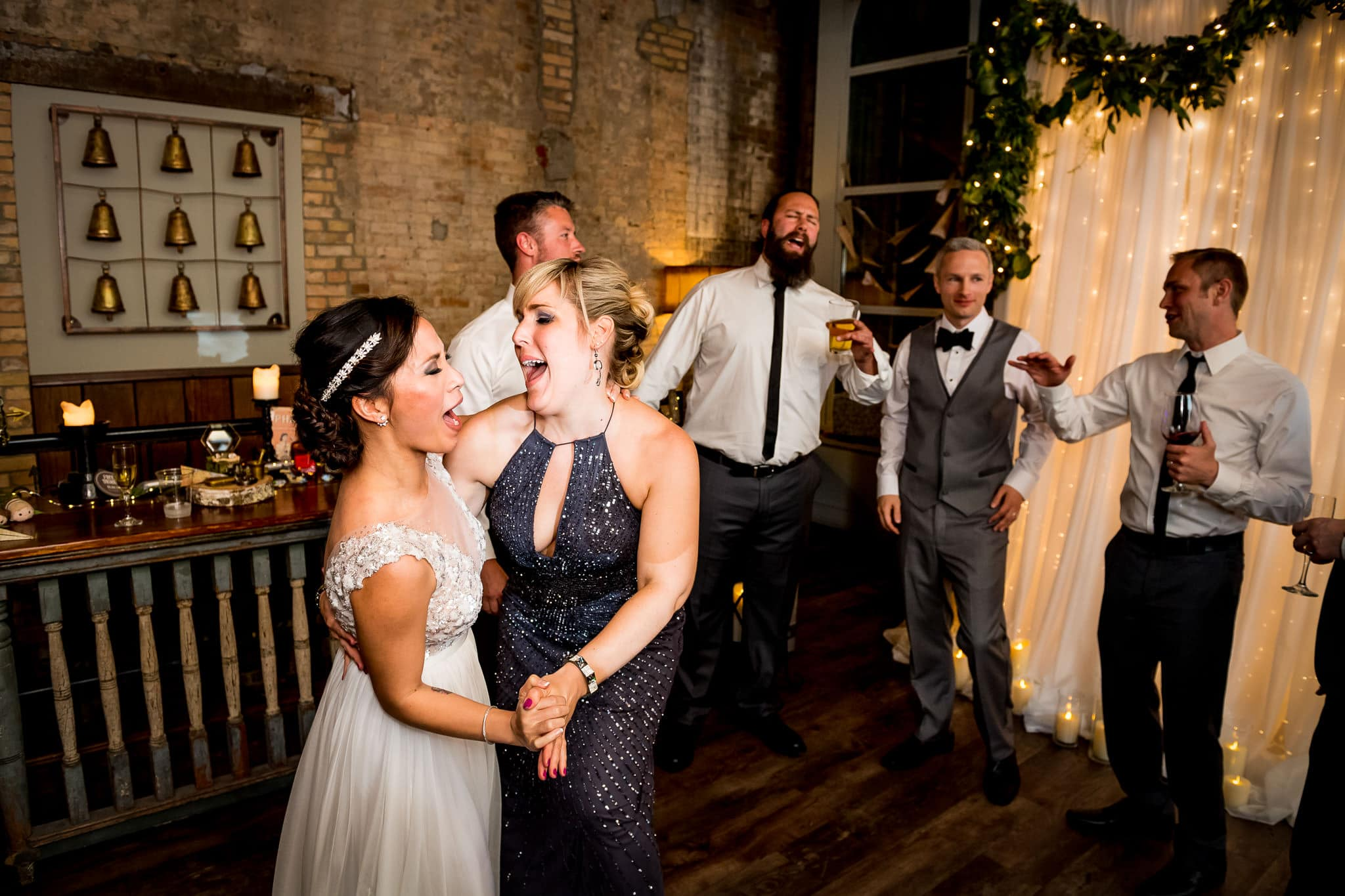 Bride and Bridesmaid sharing a fun moment on the dance floor in the River Room at Aster Cafe