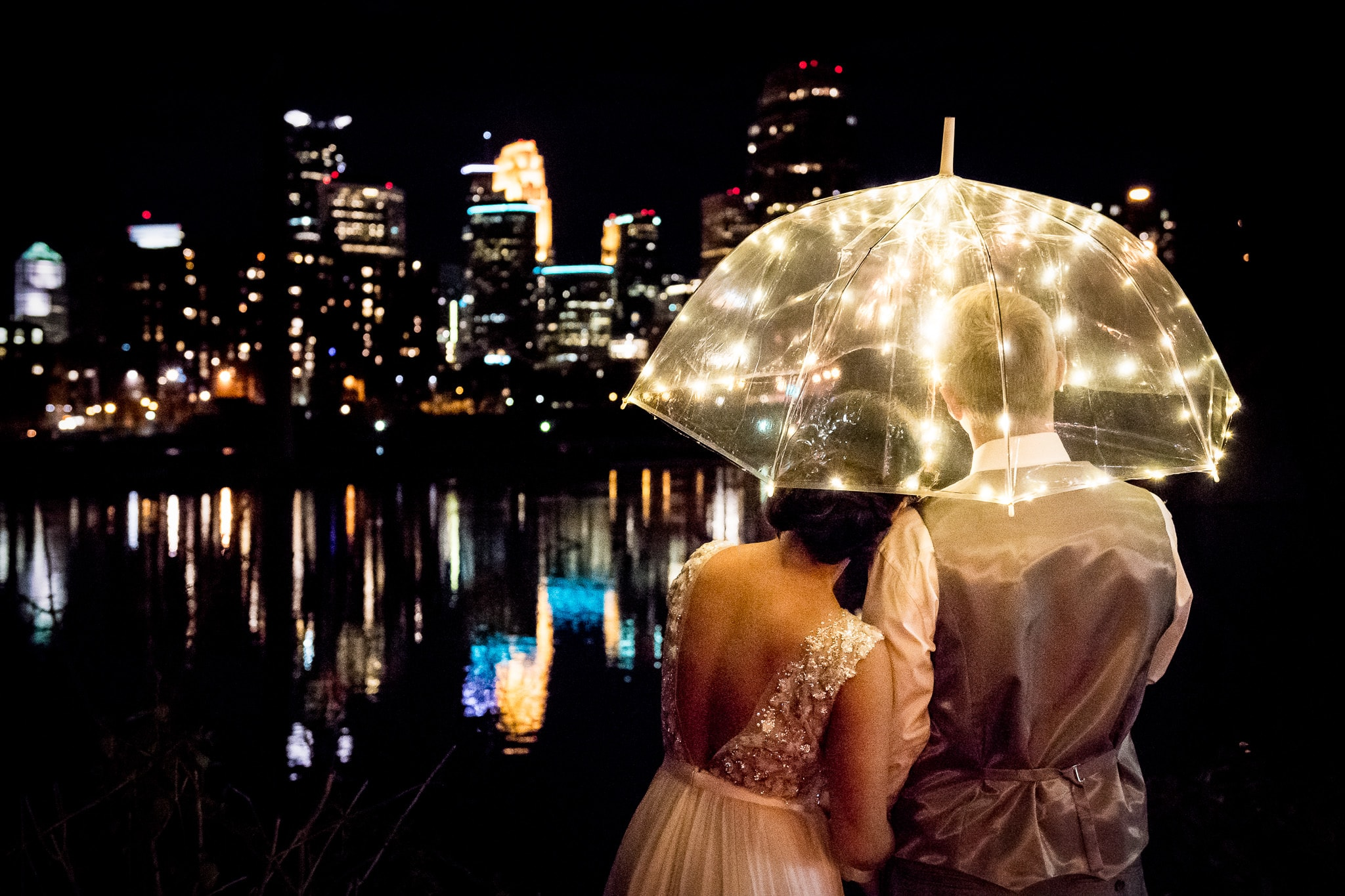 Couple embracing under an umbrella with the downtown Minneapolis skyline in the background