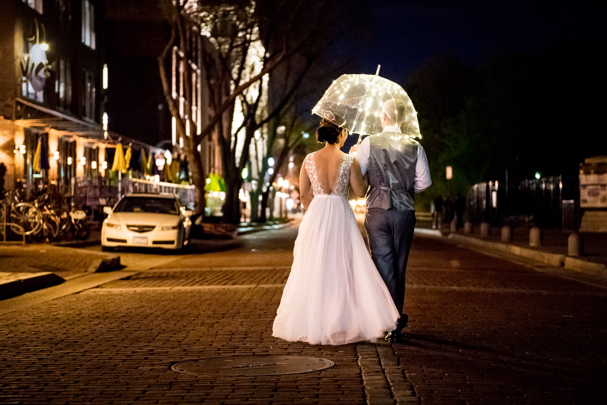 Bride and Groom walking on Main Street under a lit up umbrella just outside of Aster Cafe