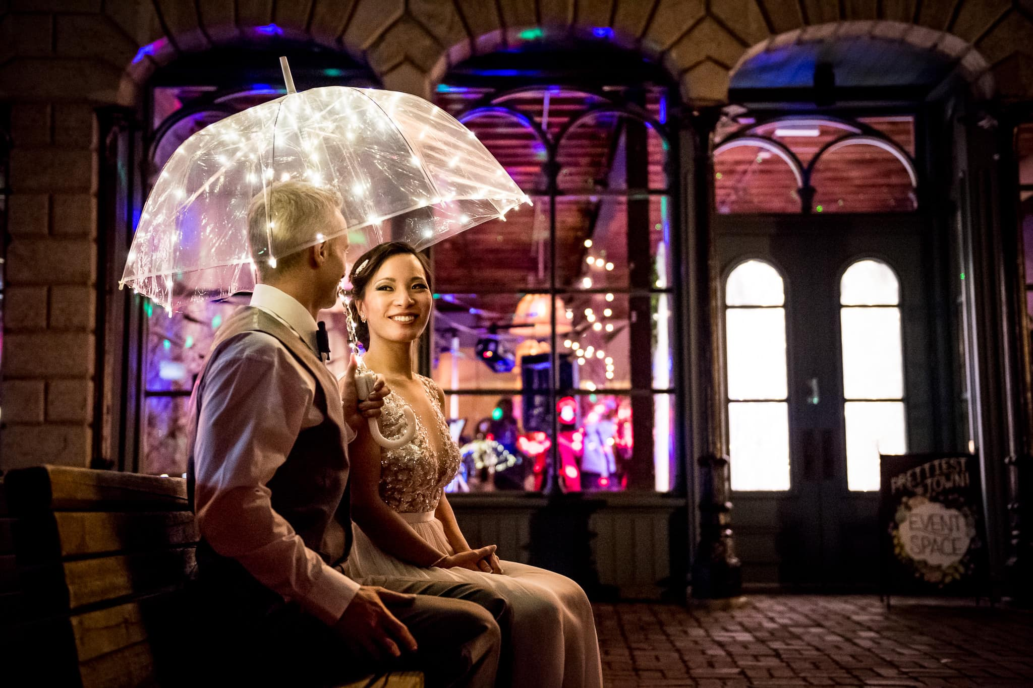 Colorful scene with the Bride and Groom sitting on a bench underneath a lit up umbrella just outside of Aster Cafe on their wedding day with a view of their wedding reception seen thru the large windows behind them