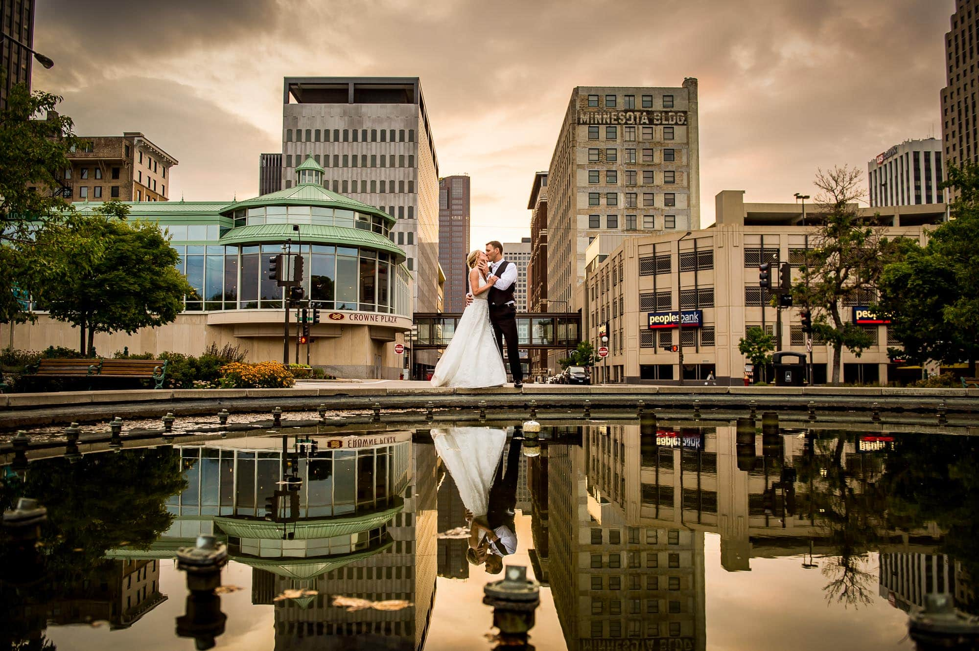 Wedding Photography displaying a Bride and Groom kissing with downtown Saint Paul, Minnesota in the background with their reflection over the water fountain at sunset.